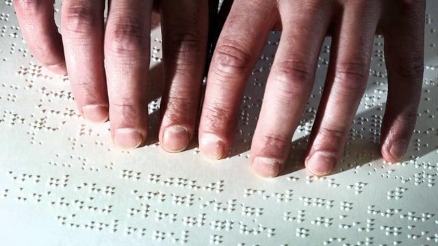Die Finger eines Mannes steichen über ein Blatt mit Braille-Schrift.