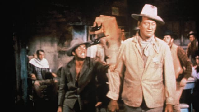 Zwei Männer mit Cowboyhut stehen in einem Saloon. Der Mann rechts trägt einen Sheriffstern an der Brust.