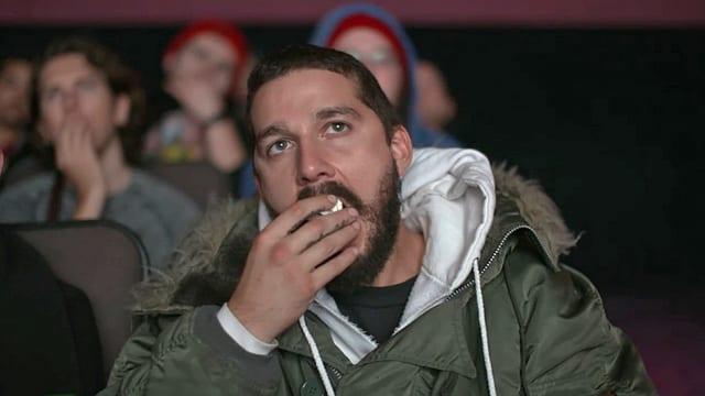 Shia LaBeouf isst Popcorn und sitz in einem Kinosessel.