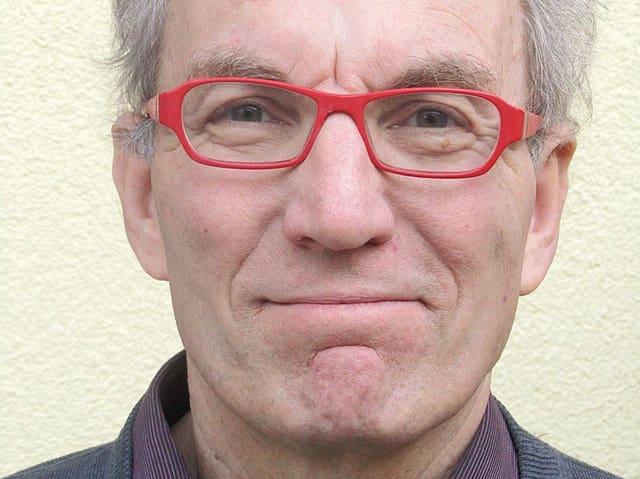 Porträt von Roland Stark mit roter Brille.