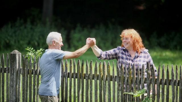 Ein Mann und eine Frau geben sich über einen Gartenzaun die Hand.