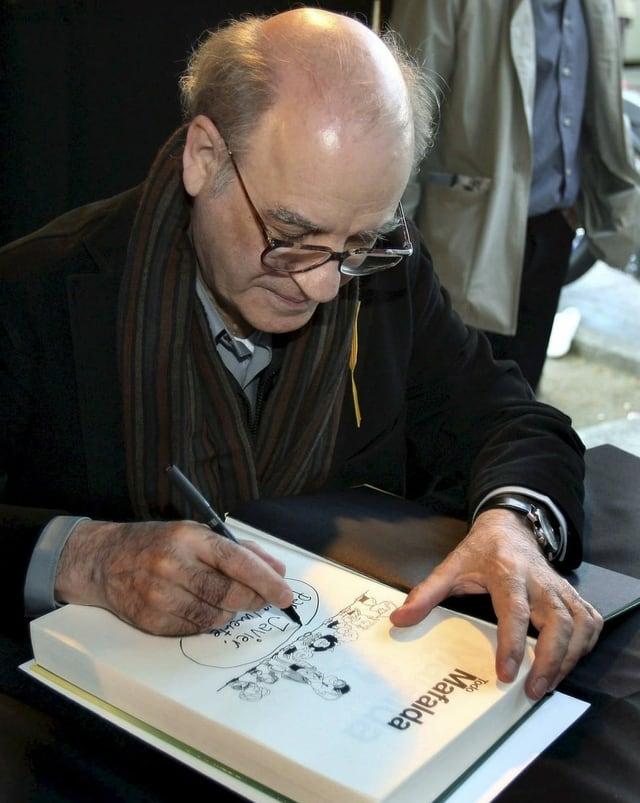 Älterer Herr signiert ein Comicbuch.