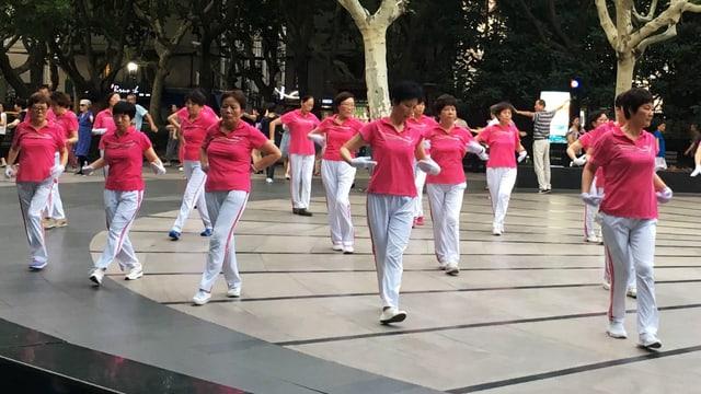 Tanzende Frauen, alle mit pinkem T-Shirt, weisser Hose und wiessen Handschuhen