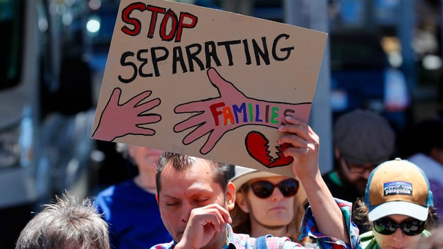 Demonstrat, der ein Plakat hochhält. Darauf steht: «Stop Separating Families»