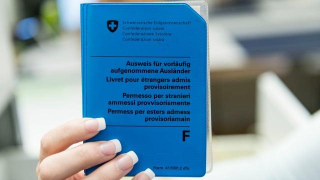 Eine Frau hält einen Ausweis in der Hand.