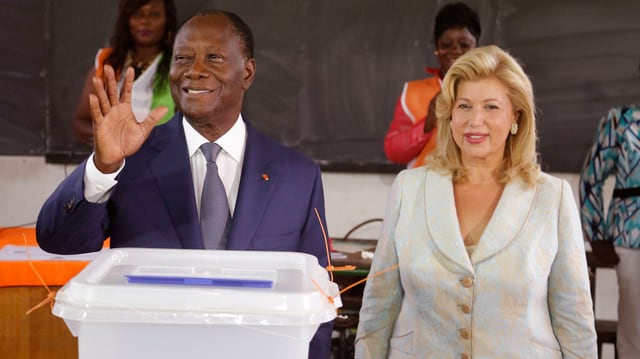 Alassane Ouattara und seine Frau Dominique Ouattara vor einer Urne