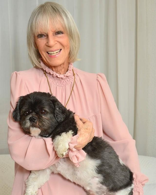 Eine lachende Frau mit einem Hund in den Armen.