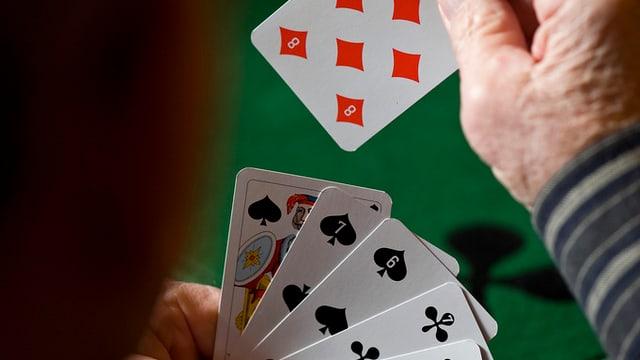 Ein Mann hält Spielkarten in der Hand.