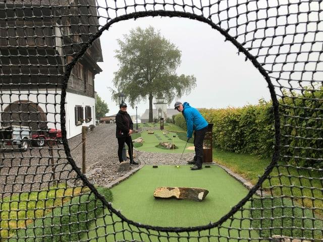 Zwei Menschen spielen einen Minigolfball durch ein Netz.