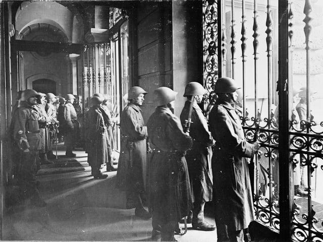 Hinter geschlossenen Gittern stehen Soldaten und blicken auf den Bundshausplatz.