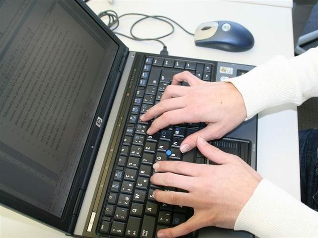 Ina persuna che scriva sinil laptop.