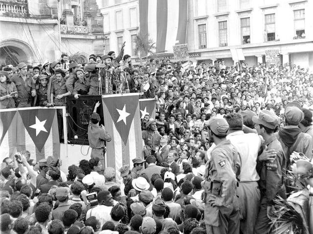 Castro steht auf einer Bühne, darunter Tausende Menschen