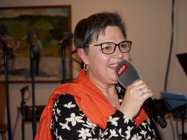 Moderatorin mit rotem Schal.