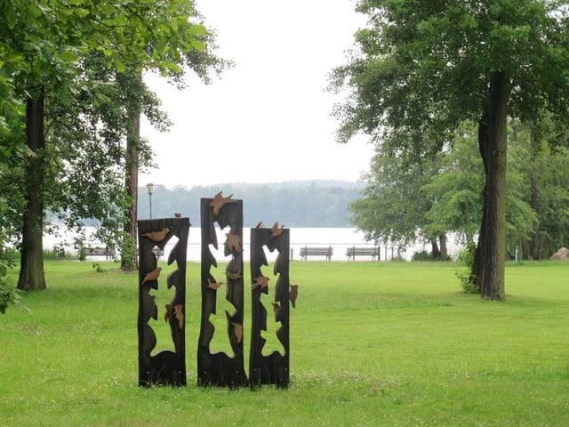 Eine Skulptur auf einer Wiese. Im Hintergrund der Scharmützelsee.