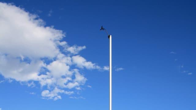 Aufnahme eines Windmastes im Tessin unter blauem Himmel.