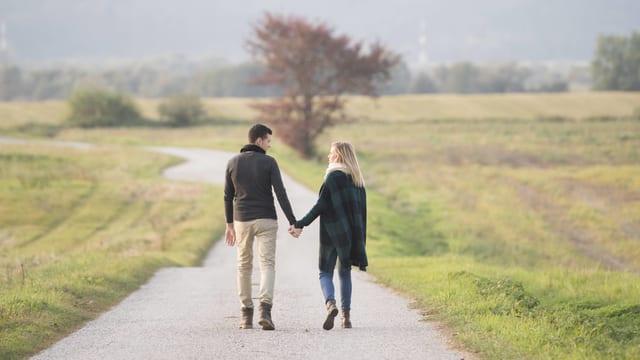 Ein Paar geht Hand in Hand spazieren.