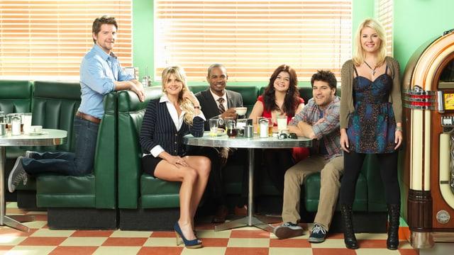 Drie Frauen und drei Männer sitzen in einem Lokal rund um einen Tisch.