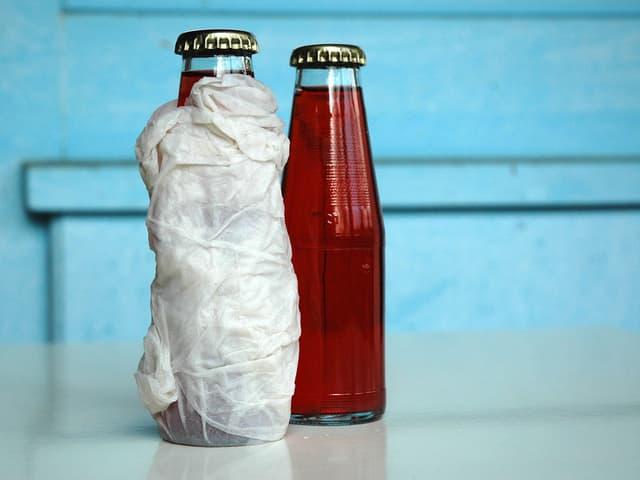 Zwei Flaschen auf einem weissen Tisch, um die eine ist ein feuchtes Haushaltspapier gewickelt.
