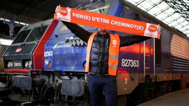 Ein Bahn-Angestellt hält ein Banner in die Luft, darauf steht: «Stolz, Eisenbahner zu sein.» (reuters)