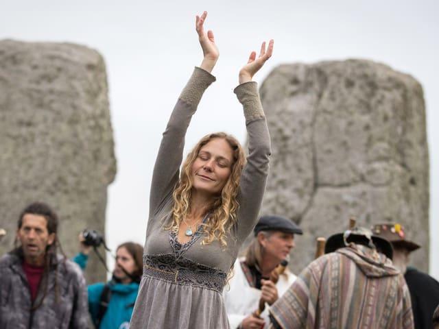 Frau steht mit erhobenen Händen und geschlossenen Augen vor Steinkreis