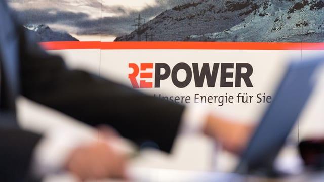 Logo da la Repower davos ina persuna che lavura vid il laptop.