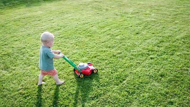 Ein Kind mäht den Rasen mit einem Spielzeugrasenmäher.