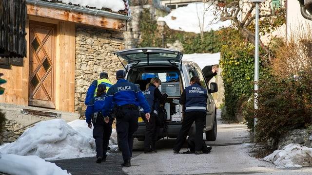 Walliser Kantonspolizisten hinter einem Fahrzeug in enger Gasse