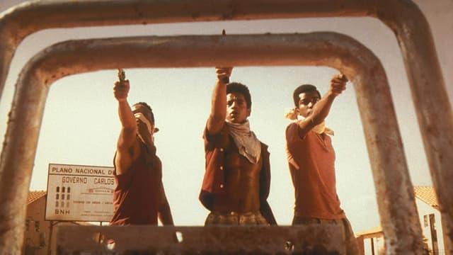 Drei junge Männer mit Pistolen stehen vor einem Metallgebilde.