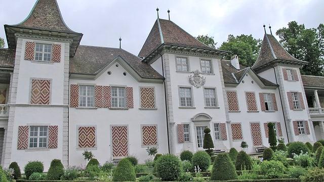 Schloss von aussen mit dem Garten im Vordergrund.
