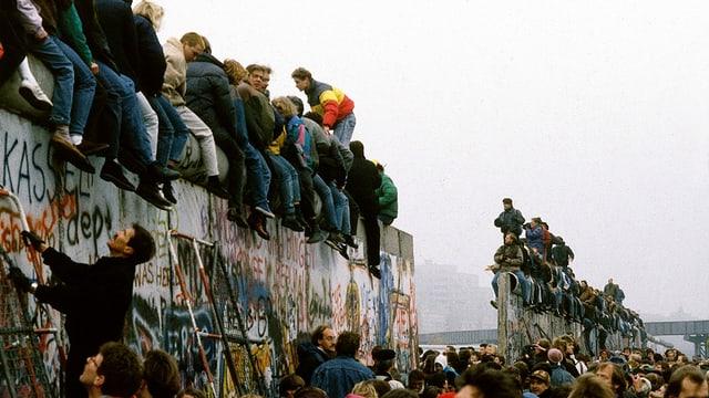 Menschen auf der Mauer sitzend.
