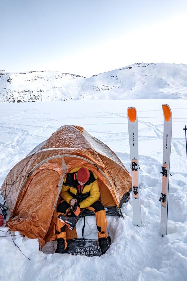 Ein Mann kommt aus einem orangefarbigen Zelt heraus