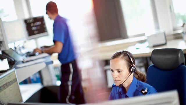 Zwei Polizeibeamte arbeiten in der Notrufzentrale mit Kopfhörern und Mikrofon an Computern.