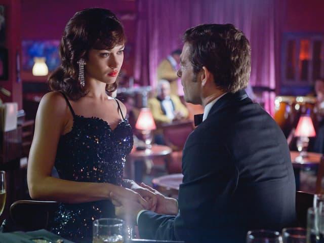Filmszene: Kurylenko in glitzerndem Kleid spricht ion einer Bar mit einem Mann.