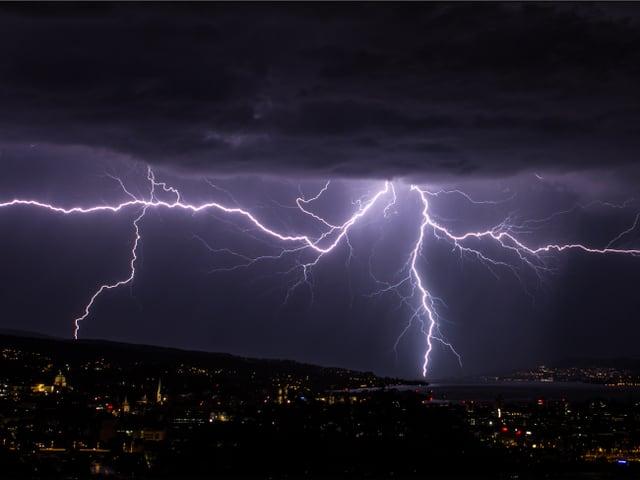 Dunkle Nacht, der Himmel ist dunkelviolett erhellt von vielen Blitzen.