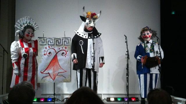 Drei Personen in Schnitzelbank-Kostümen auf der Theaterbühne.