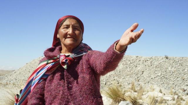Eine peruanische Bäuerin zeigt auf die Umgebung, die von der Mine verschmutzt wird.