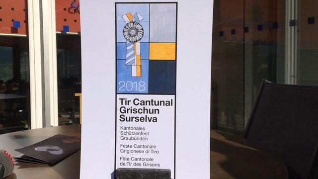 Il logo mussa il Chardunet d'argient (Silberdistel) cun bindels en la colurs grisch mellen e blau sco il vopna dal chantun Grischun.
