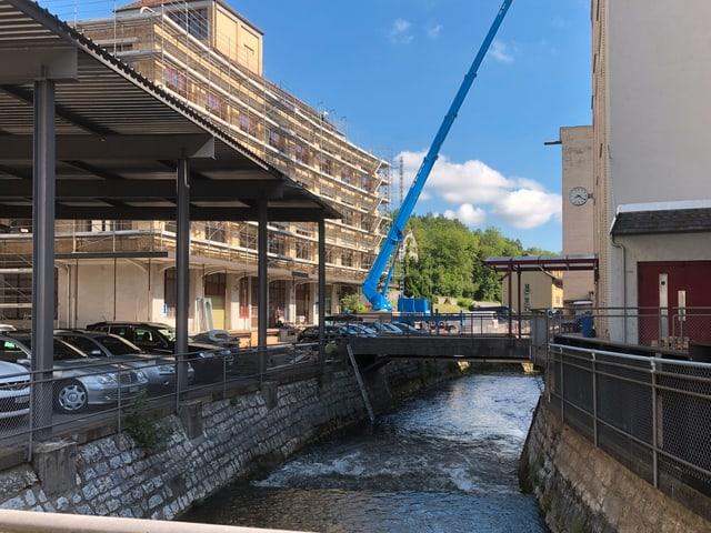 Ein Fluss in der Mitte, rechts ein altes Industriegebäude, links ein gedeckter Parkplatz.