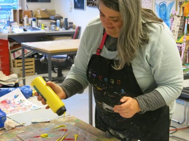 Eine Frau mit langen Haaren spritzt gelbe Farbe auf eine Plexiglas-Unterlage.