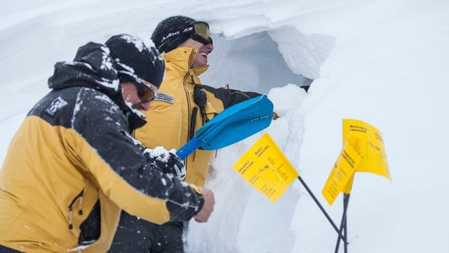 Zwei Retter suchen im Schnee