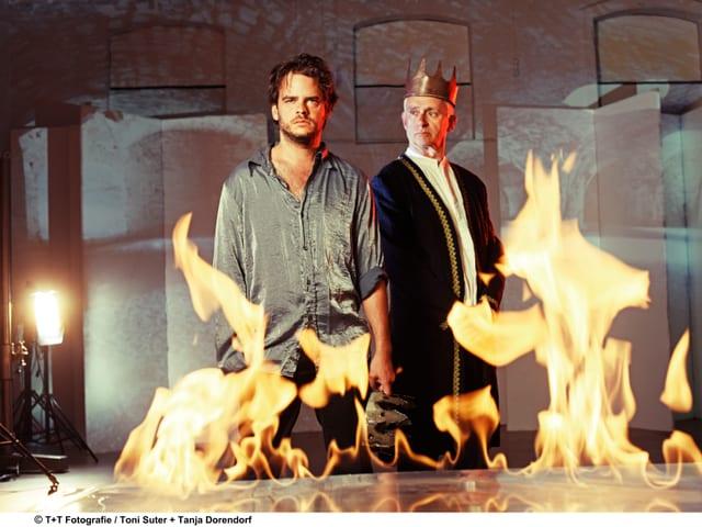 Die beiden Schauspieler stehen hinter einem Tisch, aus dem Flammen schlagen