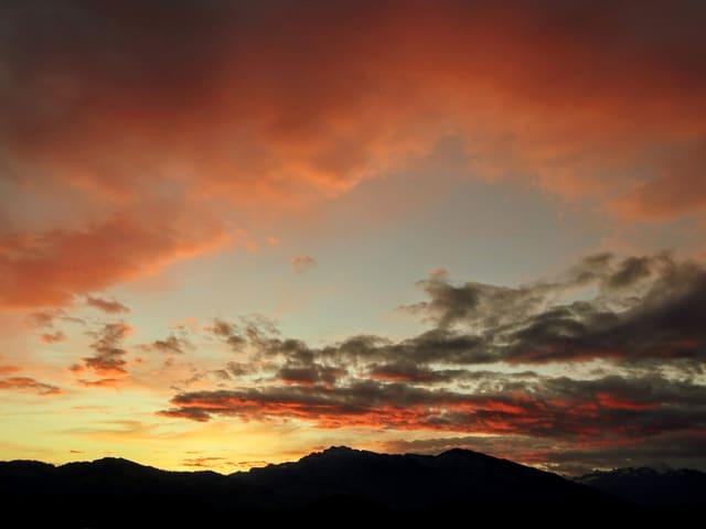 Leicht bewölkter Himmel mit roten Wolken in der Dämmerung