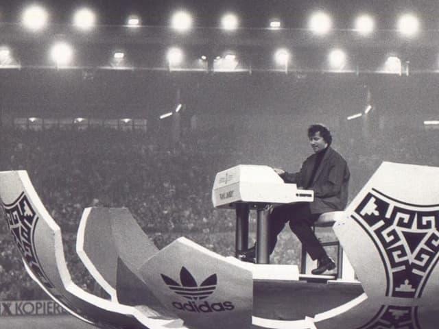 Mann spielt Hammond Orgel in aufgeklappter-Fussball-kulisse