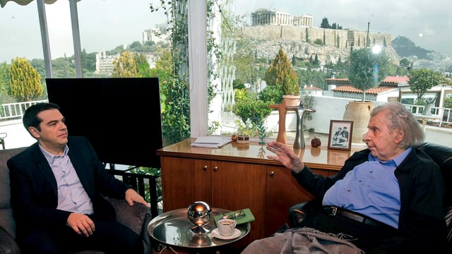 Alexis Tsipras spricht mit Mikis Theodorakis, der in eine Decke gehüllt ist.