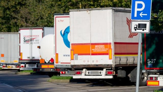 Schild Parkplatz, dahinter Lastwagen.