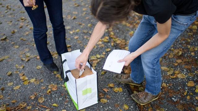 Ein Mann legt seinen Stimmzettel in eine Urne.