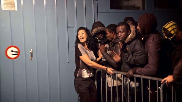 Eine Frau an einem Gitter. Auf der anderen Seite drängen sich junge Männer dagegen.