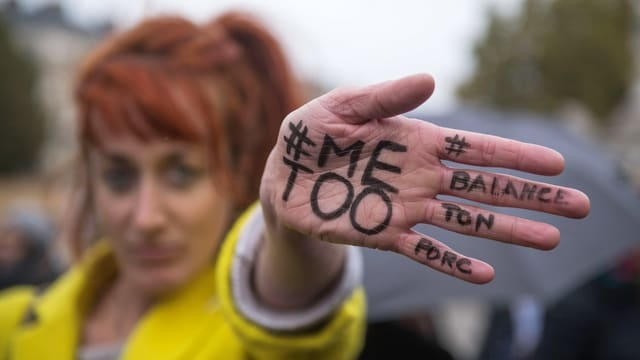 Eine Frau hält die Hand in die Linse. Darauf steht #MeToo.