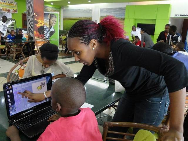 Eine Mitarbeiterin zeigt auf den Bildschirm eines Laptops, der vor einem Jungen steht.
