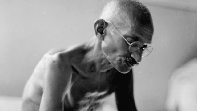 Schwarzweissbild: Gandhi mit nacktem Oberkörper und geschlossenen Augen, vornübergebeugt.